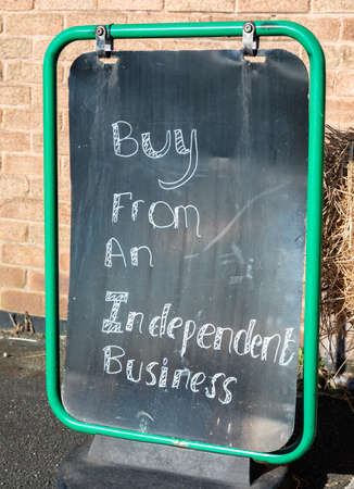 close up of a metal sign with a black background and white lettering outside a local shop encouraging people to buy from an independent business Wallasey Village February 2019
