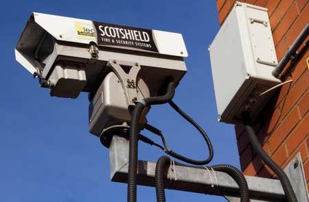 Exterior shot of a CCTV security camera on a brick wall set against a blue sky Manchester England February 2013
