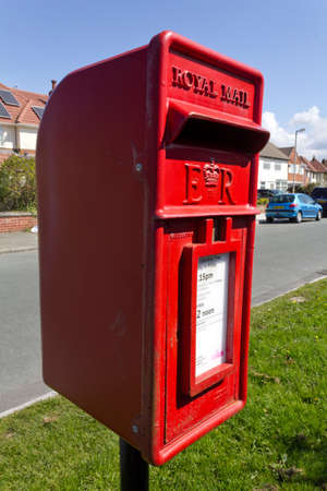 Small red Royal Mail post box on a metal pole Leasowe Wirral April 2012 Editorial