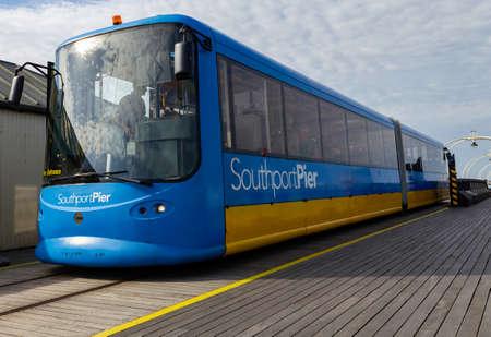 A blue passenger tram travels along Southport Pier