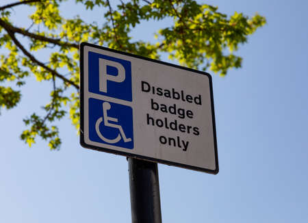 Close up of street sign with logos indicating parking for disabled badge holders only Widnes