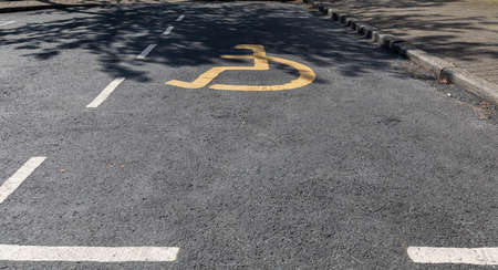yellow disabled parking sign on the road in Widnes, England Stock Photo
