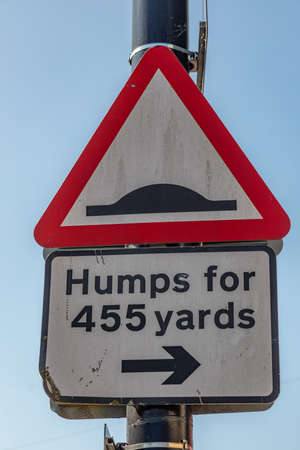 Triangular street sign warning of humps in the road Widnes