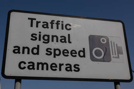 Close up of road sign warning of traffic signal and speed cameras Wirral Stock Photo
