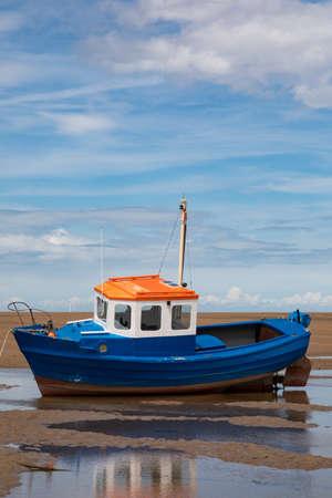 petit bateau bleu orange et blanc amarré sur la plage à marée basse à Meols juin 2019