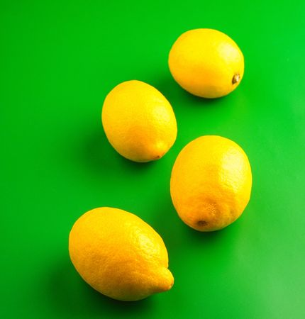 foodie: four lemons on  green background