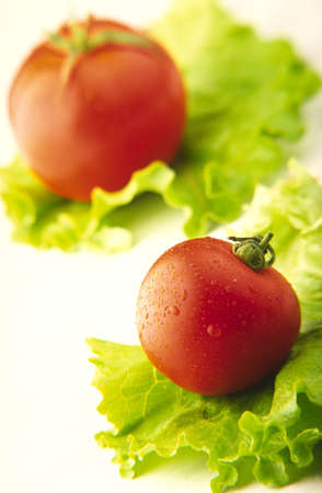 two red tomatoes on green salad leaves Banco de Imagens