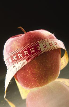 metro de medir: Manzana roja, retorcida en la medici�n de metros sobre fondo negro