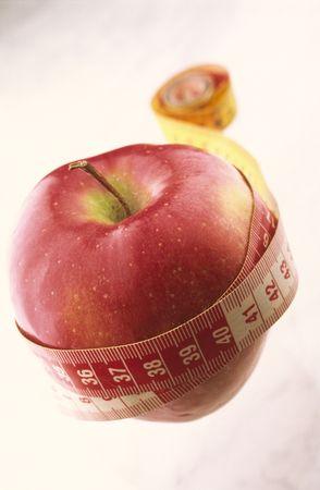 metro de medir: La manzana roja torci� en metro que med�a en el fondo blanco