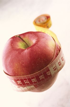 favourable: Red apple twisted in measuring meter on  white background Stock Photo