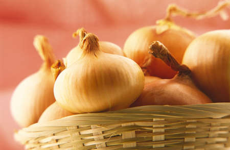 close up of onions in a basket: basket of onions on  red background