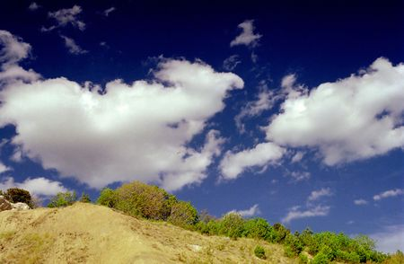 breakage: Dark blue clouds above breakage covered with greens Stock Photo