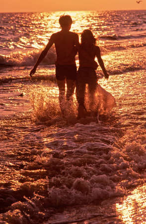 pair young people goes along seacoast towards to  coming sun photo