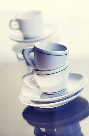 washed pure utensils, coffee cups and plates on light background photo