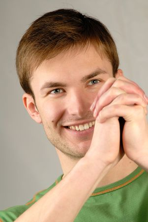 gesticulation: Portrait of  smiling young guy and  compressed hands,  close up