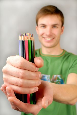 finders: young guy holds  set of multi-coloured pencils in hands Stock Photo