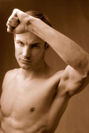 Young  man does sports exercises having lifted above  head  hand Stock Photo - 1080058