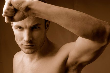 hand lifted: Young  man does sports exercises having lifted above  head  hand