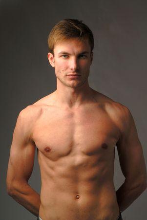 uomini nudi: Ritratto di giovane nudo maschile che guarda in camera su sfondo scuro
