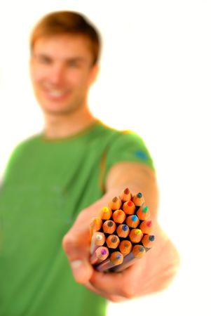 finders: guy suggests and holds  set of color pencils in  hand on  white background