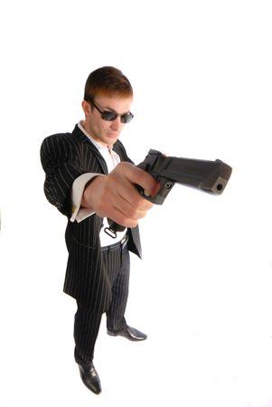 sicario: Hombre joven en traje negro con una pistola en la mano