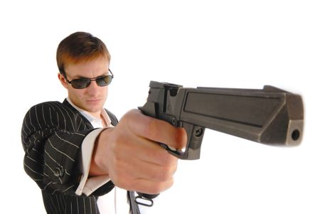 armed services: Young  man in  black suit with a pistol in  hand, close up