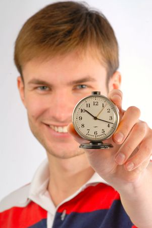 time critical: young nice, smiling guy with an alarm clock in hands, close up