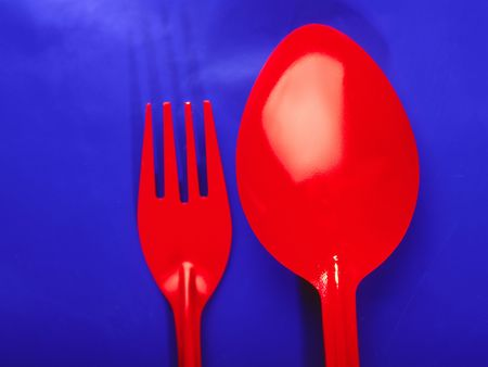 Brightly red spoon and plug on  dark blue background, close up photo