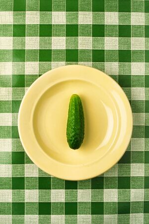 Green juicy cucumber in  yellow plate on  background of  green cloth photo