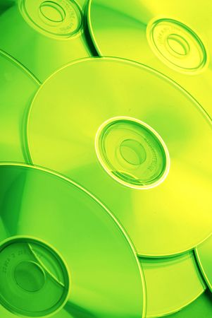 Many compact disks covered by green light, close-up Stock Photo