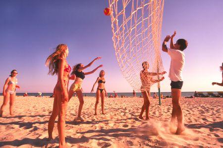 La gente joven juega a voleibol en la playa en día asoleado caliente