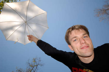 young guy with  white umbrella above  head on  background of  dark blue sky photo