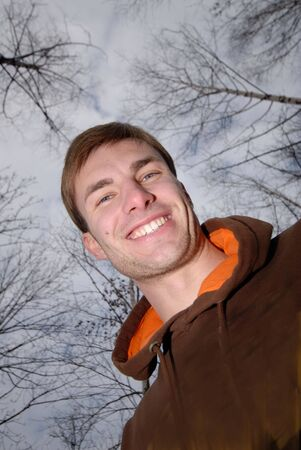 Portrait of  smiling young man on  background of trees photo