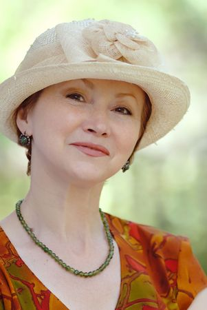 portrait of  woman in  age of in  hat on  light green background Stock Photo