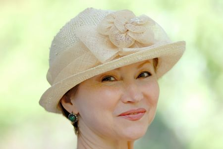 portrait of  woman in  age of in  hat on  light green background photo