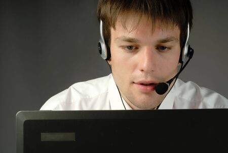 young businessman works in headphones with  microphone behind  computer Stock Photo