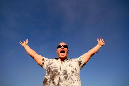 guy in glasses shouts on  background  dark blue sky photo