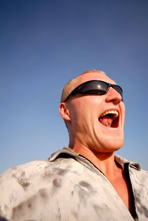 guy in glasses shouts on  background  dark blue sky, portrait photo