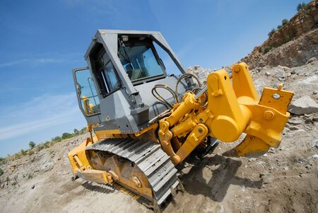 industrial bulldozer working in career on extraction photo