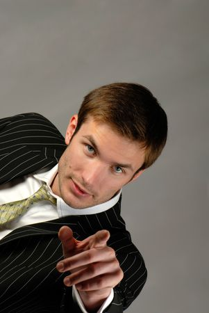 businessman emotionally gesticulates hands on  grey background Stock Photo
