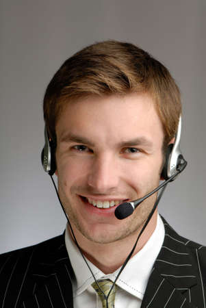 young businessman in headphones speaks on  microphone on  grey background
