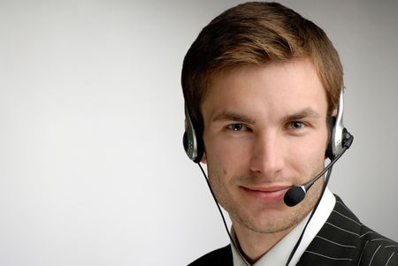 operators: young businessman in headphones speaks on  microphone on  grey background