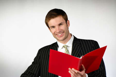 businessman looks  folder of red color with documents on  gray background