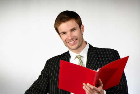 hombre de negocios mira la carpeta de color rojo con documentos sobre fondo gris  Foto de archivo - 2025514