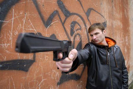 壁の背景に手でピストルを持つ若い男