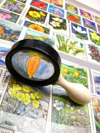 varied: old magnifying magnifier and collection of stamps, close up Stock Photo