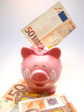 piggy bank and fifty euro on a white background, close up photo