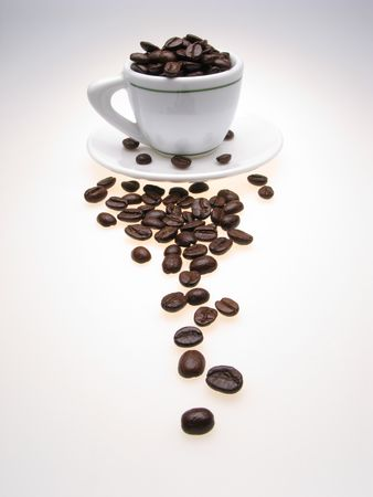 white color  cup and  plate filled with grains of coffee on  light background, close up photo