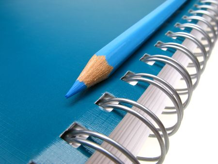 blue pencil and spiral of  notebook on  light background,  close up
