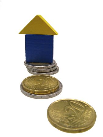 accumulation:  isolated toy house on coins of euro,  close up